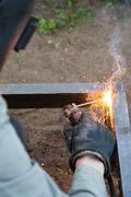 Worker in protective mask welding steel railings outdoors - stock photo