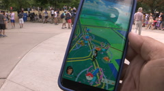 Crowds of people playing Pokemon GO in Toronto Stock Footage