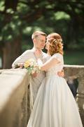 Beautiful romantic wedding couple of newlyweds hugging in park on sunset Stock Photos
