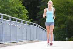 Woman runs outdoor on a bridge as stamina training Stock Photos