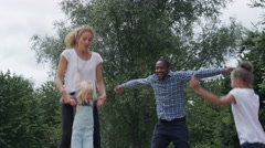 4K Happy mixed race family having fun, jumping on inflatable at activity centre Stock Footage
