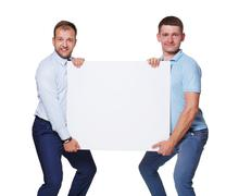 Two businessmen carry and show blank advertising board, isolated Kuvituskuvat
