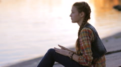 Teen girl relaxing by lake at sunset and having fun clapping music rhythm Stock Footage