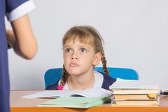 Schoolgirl sitting at the desk angrily looks at another girl Stock Photos