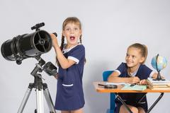 Girl surprised astronomer observing through a telescope, the other girl looke Stock Photos