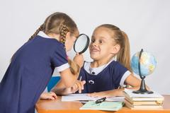 Girl looking at the other girl with a magnifying glass on a geography lesson Stock Photos
