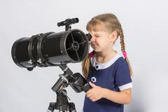 Girl amateur astronomer sets up a telescope for observing the starry sky Stock Photos