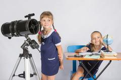 Girl astronomer looks at the sky, the other girl sitting happily at the table Stock Photos