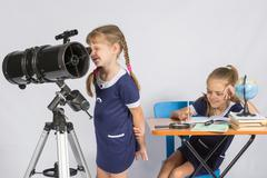 Girl astronomer looks through the eyepiece of the telescope, and the other gi Stock Photos