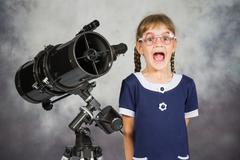 Girl astronomer happily surprised by what he saw in the telescope - stock photo