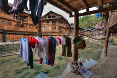 Wet laundry drying on hangers under cover outdoors, Guizhou, China. Stock Photos