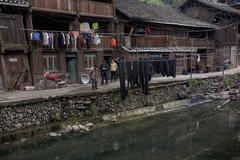 Wooden farmhouses Chinese peasants are located on banks river village. Stock Photos