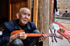An elderly Chinese man holds local music stringed instrument, China. Stock Photos