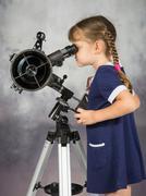 Girl amateur astronomers looking into the telescope eyepiece Stock Photos