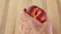 Man peels fresh peach Stock Footage
