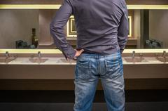 Man adjusts after peeing on the public toilet in restroom Stock Photos