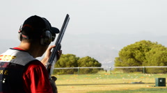 Shooter man skeet aiming and firing a rifle in a competition of skeet. Stock Footage