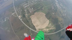 Skydivers with colorful parachutes fly over field. Extreme active sport. Tandem - stock footage