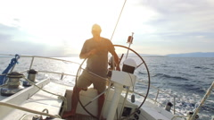 Man is steering his big sailboat on the sea on a sunny evening Stock Footage