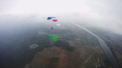 Skydivers with colorful parachutes fly over green field in cloudy sky. Extreme - stock footage