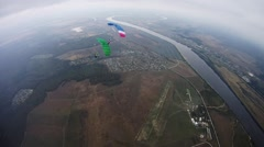 Skydivers with colorful parachutes balance in sky over green field. Tandem - stock footage