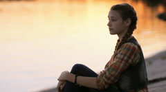 Sad pensive teen girl puts chin on hand while sitting on the beach at sunset Stock Footage