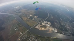 Skydivers parachuting in sky over green field. Extreme. Cloudy evening - stock footage