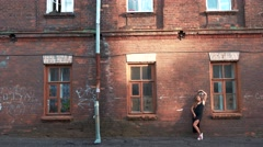 Beautiful Woman posing at the Old Brick building Stock Footage