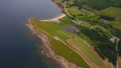 Aerial shot of field and rocky ocean coast in Cape Breton - stock footage