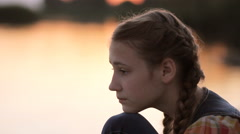 Sad teen girl resting her chin on her knee sitting on beach at sunset Stock Footage