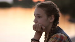 Sad teen girl resting chin in hand thinking sitting by calm lake at sunset Stock Footage