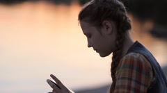 Pretty teen girl using app on mobile phone during recreation time by the river Stock Footage