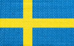 Flag of Sweden on brick wall texture background. Swedish national flag. Stock Illustration