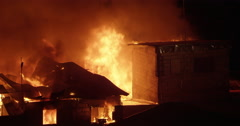 House being consumed by fire inferno in poor settlement Stock Footage