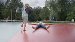 4K Little girls having fun, jumping on inflatable at outdoor activity centre Stock Footage