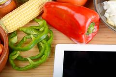 Vegetables and seasonings with a digital tablet. Stock Photos