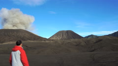 Backpacker male traveler walking around active smoking Bromo volcano Stock Footage