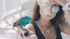 Girl in black smoking e-cigarette, resting on lounge and looking aside - stock footage