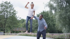 4K Father & daughter having fun, jumping on inflatable at activity center Stock Footage