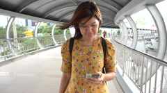 Asain Woman walking while  looking on the mobile in the city Stock Footage