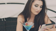 Stylish girl in using mobile phone at the beach table with cocktail Stock Footage
