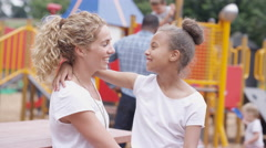 4K Portrait smiling mixed race mother & daughter at outdoor adventure playground Stock Footage