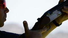 Shooter face aiming and firing a rifle in skeet Stock Footage