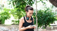 Closeup of Eurasian woman putting on headphone after selecting playlist Stock Footage