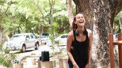 Eurasian woman laughs at the camera after high knee exercise Stock Footage