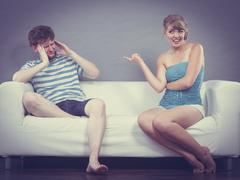 Man and woman having argument sitting on sofa at home Stock Photos