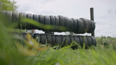 4K Competitors in endurance race helping each other through tyre obstacle Stock Footage