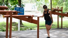 Eurasian woman stretching her thighs with support from railing Stock Footage