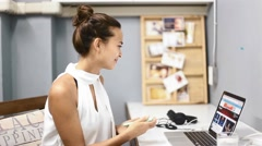 Eurasian woman talks on the phone while scrolling through her laptop Stock Footage