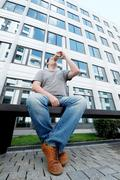 City style. Handsome adult man in casual wear holding drinking  coffee in fro Stock Photos